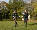 Happy sisters running in autumn park Royalty Free Stock Image