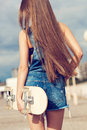 Happy skater girl young trendy beautiful woman walking on street and holding skateboard behind her head the in joyful feelings Stock Photos