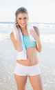 Happy slender blonde in sportswear on the phone a sunny beach Royalty Free Stock Image
