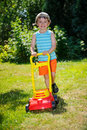 Happy small boy help with gardening with his lawn mower Royalty Free Stock Photo