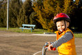 Happy small boy out riding his bicycle wearing a safety helmet and orange high visibility jacket giving the camera a lovely smile Stock Photography
