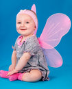 Happy small girl butterfly wings sitting on the floor Royalty Free Stock Photo