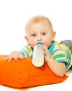Happy smart blond boy toddler drinking formula laying pillow Stock Images