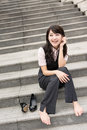 Happy smile business woman rest take off her shoe outside urban Royalty Free Stock Photos