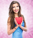 Happy smile woman holding red heart female model hold valentine day symbol pink background Royalty Free Stock Photography