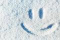 Happy smiley emoticon face in snow, winter season joy concept
