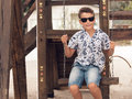 Happy smiling adolescent boy in sunglasses on a swing handsome Stock Photos
