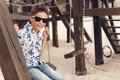 Happy smiling adolescent boy in sunglasses on a swing portrait of having fun at summer playground Royalty Free Stock Images