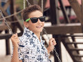 Happy smiling adolescent boy in sunglasses on a swing portrait of having fun at summer playground Royalty Free Stock Photography