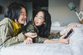 Happy smiling Asian kids on bed playing smart phone Royalty Free Stock Photo