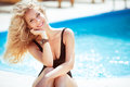 Happy smiling attractive blond woman over blue water swimming po pool beautiful model with curly hair posing at sunny day outdoor Royalty Free Stock Photo