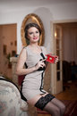 Happy smiling attractive woman wearing an elegant dress and black stockings sitting on the sofa arm holding a small red box in her Royalty Free Stock Images