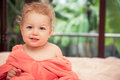 Happy smiling baby in soft pink blanket on white bed sheets in villa bedroom looking at camera with blurred tropical background Royalty Free Stock Photo