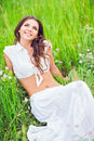 Happy smiling beautiful young woman lying among grass and flowers