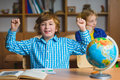 Happy smiling boy on the geography lesson in school classroom. Educational concept