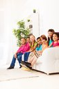 Happy smiling boys and girls together row of kids diversity looking black caucasian sitting on the couch laughing at home Stock Images