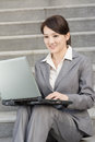 Happy smiling business woman using laptop at outside of office in modern city Stock Images