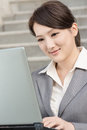 Happy smiling business woman using laptop at outside of office in modern city Royalty Free Stock Photography