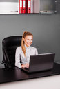 Happy smiling businesswoman typing on laptop at her desk blonde looking camera in office Royalty Free Stock Photography