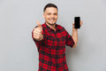 Happy casual man showing blank smartphone screen and thumb up