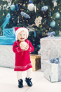 happy smiling Caucasian baby girl toddler with blue eyes in red dress and Santa Claus hat standing by New Year tree Royalty Free Stock Photo