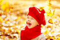 Happy smiling child in autumn park, fall yellow leaves