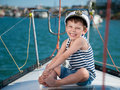 Happy smiling child captain on luxury yacht in a sea cruise Royalty Free Stock Photo