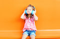 Happy smiling child enjoys listens to music in headphones over colorful orange