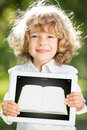 Happy smiling child holding tablet pc ebook against green spring background education technology concept Royalty Free Stock Photography