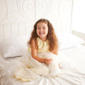 Happy smiling child waking up in the morning dream little princess on a white bed close Stock Image