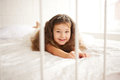 Happy smiling child waking up in the morning dream little princess on a white bed close Stock Images