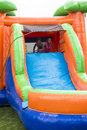 Happy smiling children playing on an inflatable slide bounce house cute diverse outdoors kids climbing up and sliding down at Stock Photo
