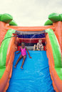Happy smiling children playing on an inflatable slide bounce house cute young outdoors diverse sliding down at outdoor Stock Image