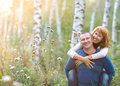 Happy smiling couple in the autumn forest sunset Royalty Free Stock Photography