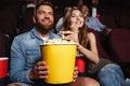 Happy smiling couple holding a big popcorn bucket Royalty Free Stock Photo