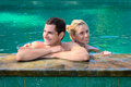 Happy smiling couple in swimming pool looking aside while relaxing on the edge of a outdoor Stock Image
