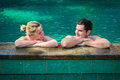Happy smiling couple in swimming pool looking on each other while relaxing on the edge of a outdoor Stock Photography