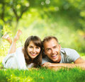 Happy smiling couple together relaxing on green grass outdoor Stock Image