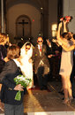 Happy smiling couple walking out of church after wedding with confetti and rose petals being thrown both have sunglasses on hers Stock Images