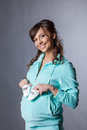 Happy smiling expectant mother posing with booties Stock Image