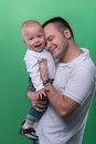 Happy smiling father embracing his baby boy half length portrait of handsome family concept isolated on green background Royalty Free Stock Images