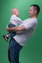 Happy smiling father embracing his baby boy portrait of handsome and son in white polo shirt looking at each other family concept Royalty Free Stock Photos