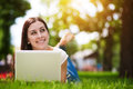 Happy smiling girl laying on grass with laptop Royalty Free Stock Images