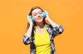 Happy smiling girl listens and enjoys the good music in headphones against colorful orange Royalty Free Stock Photo