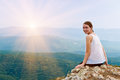 Happy smiling girl sitting on a cliff side woman relaxing in mountains at sunrise Royalty Free Stock Photography