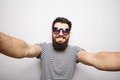 Happy smiling hipster man in glasses  taking selfie with hands on camera. Royalty Free Stock Photo