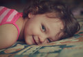 Happy smiling kid girl lying on the bed closeup vintage portrait Royalty Free Stock Photography