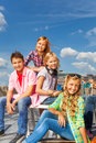 Happy smiling kids sitting close during sunny day to each other on chairs on urban background in of summer Stock Photo
