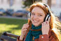 Happy smiling lady enjoying music on bench in park portrait of redhead young bright scarf the the Royalty Free Stock Photos