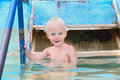 Happy smiling little boy coming into water in swimming pool warm mineral summer outdoors Royalty Free Stock Images